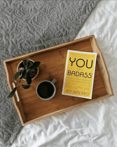 - A copy of You Are a Badass sits on a wooden tray on the right hand side. To the left of the book sits a green mug with black coffee and a plant. Half of the tray sits on a gray blanket, the other half sits on a white blanket.