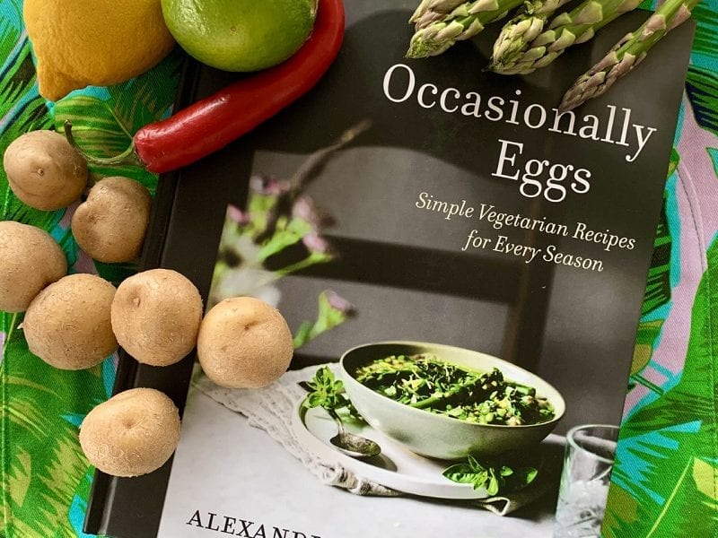 A copy of Occasionally Eggs lays on a green background surrounded by fresh fruit and vegetables