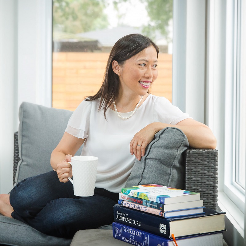 Mary Wong is sitting in a grey chair in dark blue jeans and a white t-shirt. She is holding a white mug and is looking out the window. To her right is a stack of five books.