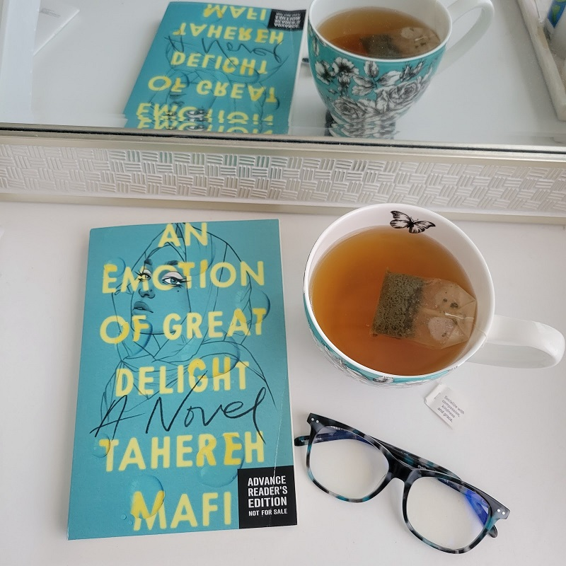 . A copy of An Emotion of Great Delight with a cup of tea and glasses.