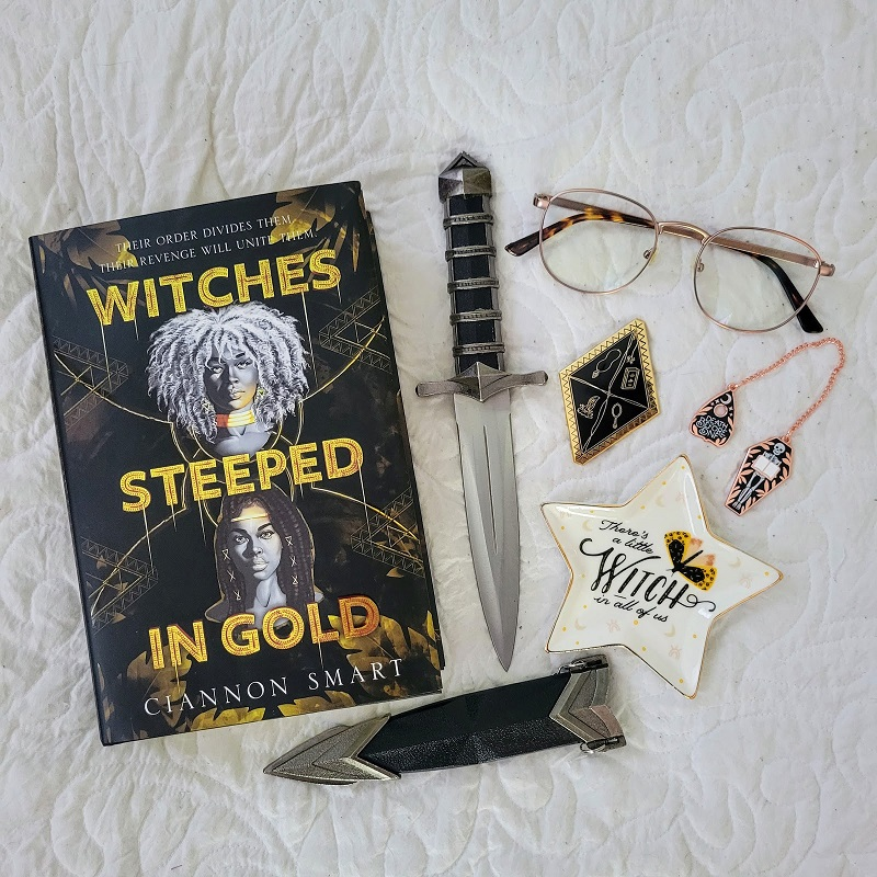 A copy of Witches Steeped in Gold with a dagger, sheath, glasses, enamel pin, chain bookmark, and jewelry dish.