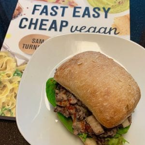 Smoky black bean and lettuce sandwich on a white plate resting on the book Fast Easy Cheap Vegan by Sam Turnbull