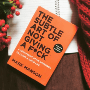 a copy of The Subtle Art of Not Giving a F*ck sits angled to the right, on top of an opened spiral-bound notebook. A bushel of holly sits on the left and a red scarf sits on the right.