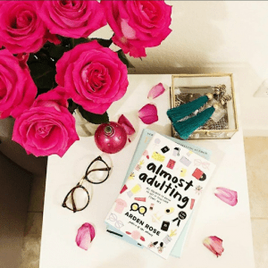 on a white table sits a pair of black-framed glasses, a bouquet of half a dozen pink roses with some petals scattered, a pink Christmas tree ornament, a gold box with teal tasselled earrings and a copy of Almost Adulting sits on top of another book.