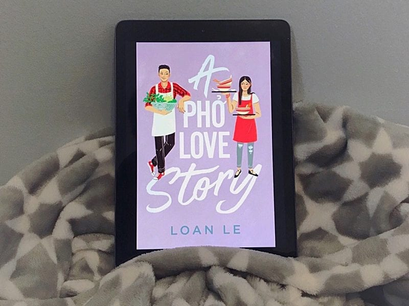 The lavender cover of A Pho Love Story is shown on an iPad screen. The iPad rests on a gray and white blanket, and leans against a blue-gray wall.