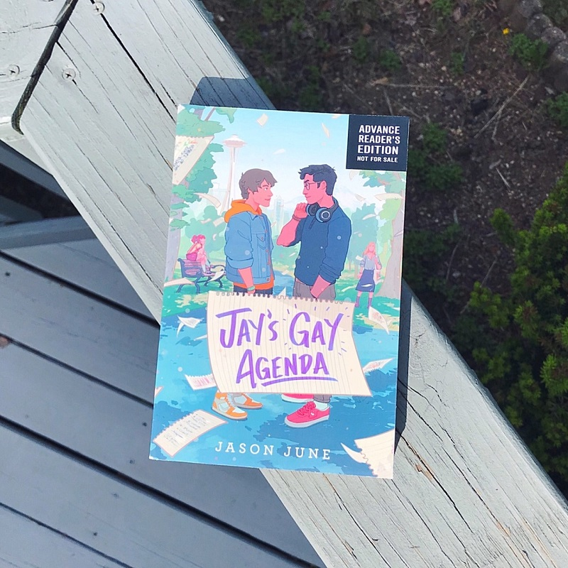 Jay's Gay Agenda sits on a light gray wood deck railing. On the left and bottom, there's the distant light gray deck floor, and on the right and top, there's the dark green and brown of an unkempt garden.