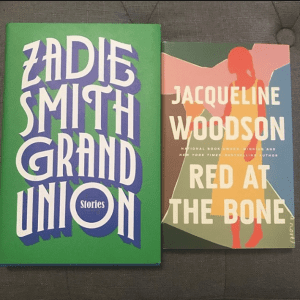 On a gray couch, two books lay flat. On the left, Grand Union by Zadie Smith sits next to Red at the Bone by Jacqueline Woodson on the right.