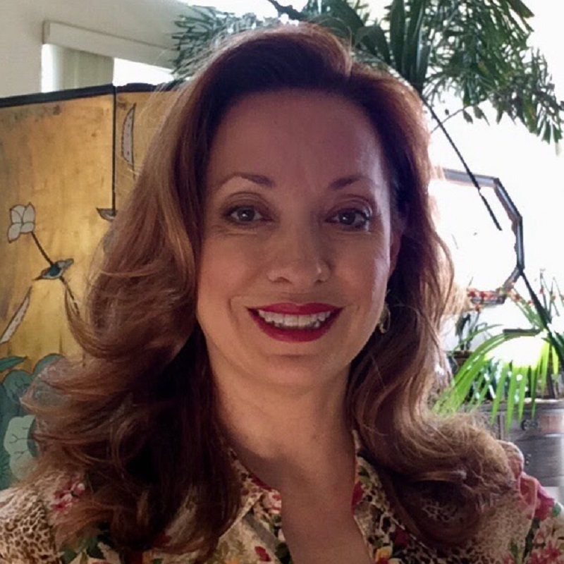 The author, Jan Moran, is centred. She has shoulder length brown hair, is wearing red lipstick and has on a cream-coloured floral shirt with leopard print. Behind her is a wooden cupboard with a floral design, tall green plants and a window.