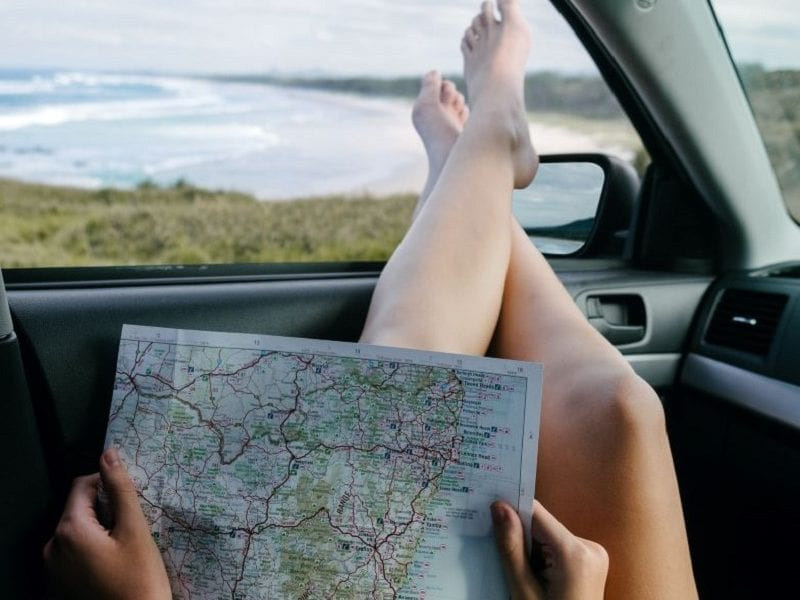 """""""woman laying back in a car with crossed feet out the window and a map in her hands. Beachfront in the background.""""Summer Self-Care Staycations in Ontario"""