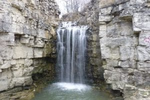 """""""a waterfall flows from a rock cliff with trees in the background."""