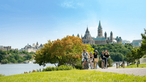 five people bike along a path with trees, grass and a waterway to the left and the Ottawa parliament buildings in the background.Summer Self-Care Staycations in Ontario