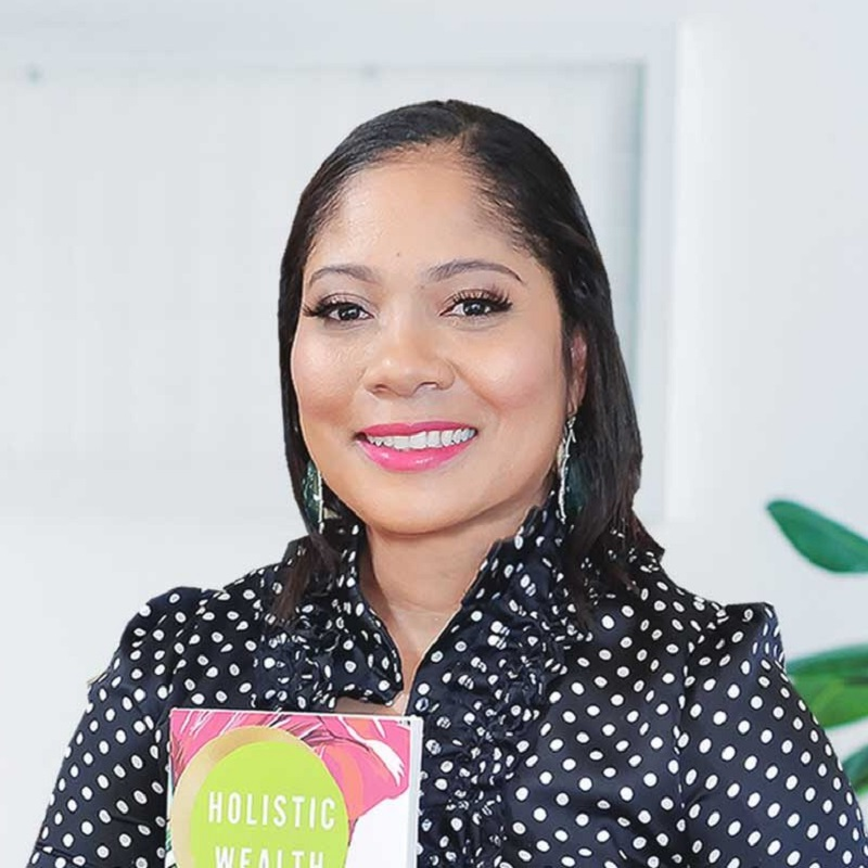 : Keisha Blair, author of Holistic Wealth, stands off centre in a black and white vertical striped shirt and large silver and blue earrings. To the left is a tall, black vase. To her right is a glass ornament where a copy of her book leans. The wall behind her is white with grey and blue decorative print.