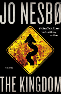 a full-frame image of the book, The Kingdom By Jo Nesboø is shown. The cover is black with white writing. In the middle of the book cover is a yellow sign with a black curving arrow.