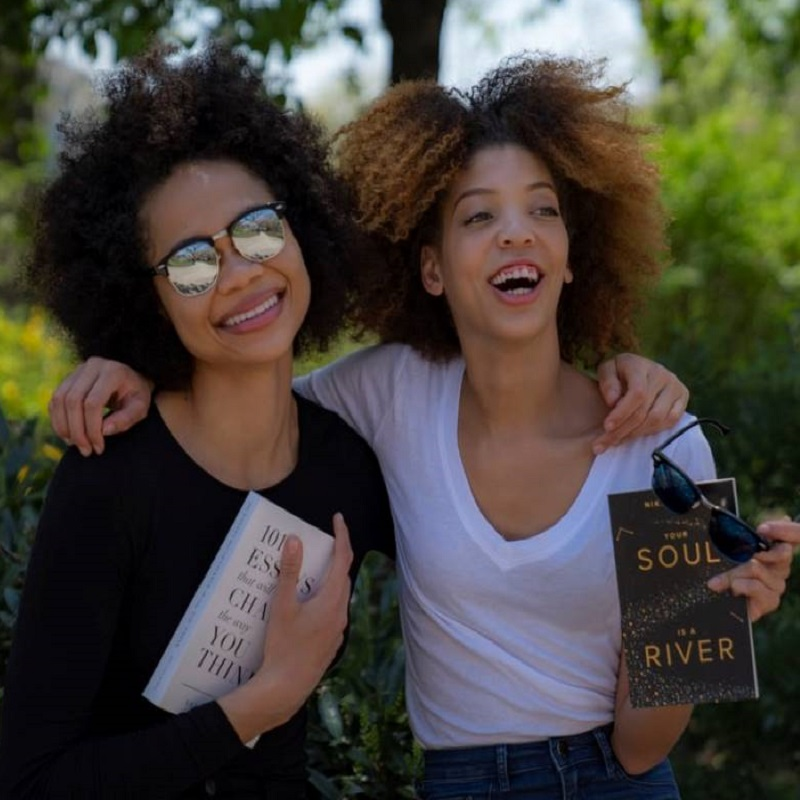 "one woman and one girl standing with arms around each other smiling and holding books"" - What Makes a Good Book Club Book?"