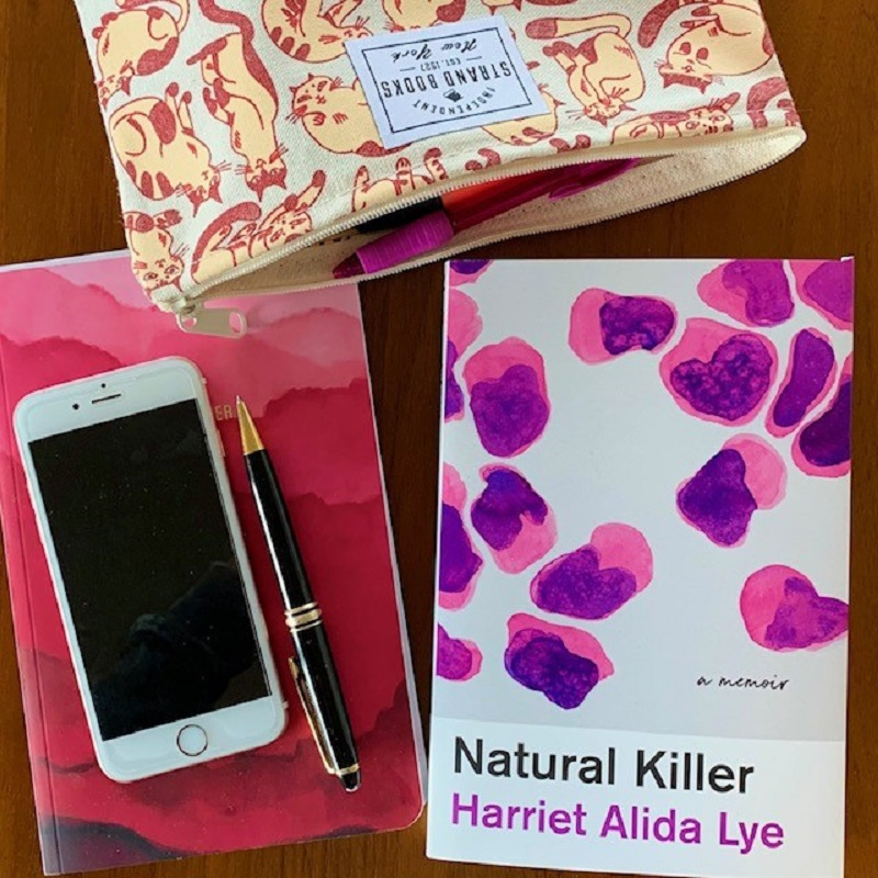 A copy of Natural Killer by Harriet Alida Lye next to a notebook, pen, pencil case and cell phone on a desk