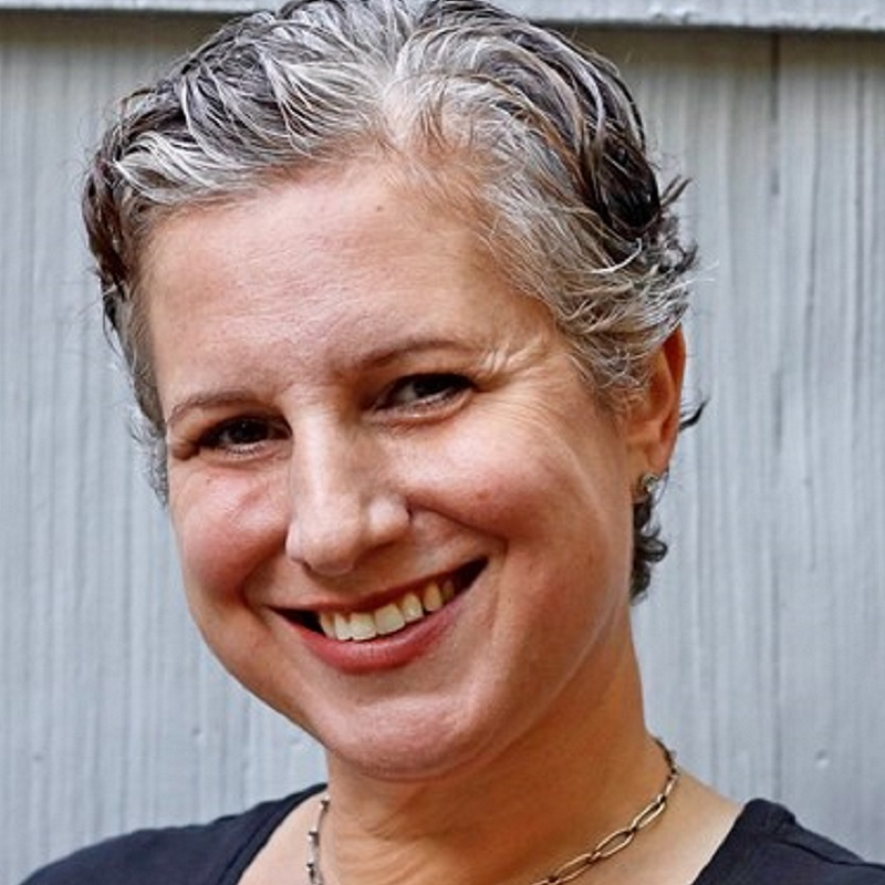Elisa Udaskin is smiling, wearing a black crew-neck shirt, with a silver necklace that has a starfish pendant on it. She is standing in front of a white background.