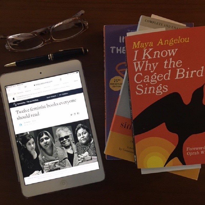 Photograph of iPad showing UN Women article next to some reading glasses, a pen and a selection of books including I Know Why the Caged Bird Sings by Maya Angelou