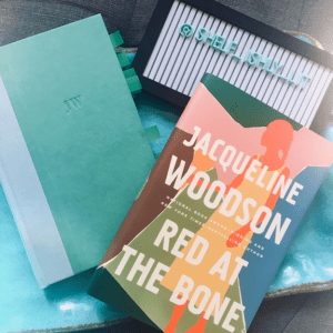 A blue blanket sits on a gray couch. On top of the blue blanket sits the hardcover book Red at the Bone by Jacqueline Woodson with sticky-note tabs sticking out. The book sits bare, with the book jacket laying on top, just to the right. Behind the book cover sits a black-framed sign that reads @shelf_ishly_lit in turquoise letters on a white background.