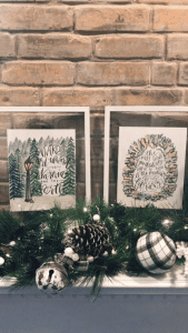 2 prints in frames on mantle with decorative greenery and brick wall.