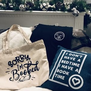 : Book tote, pillow and shirt displayed on a blanket in front of decorative greenery.