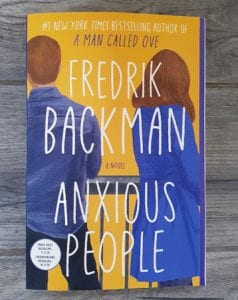 On a wooden surface, the book Anxious People by Fredrik Backman lies flat in the centre.