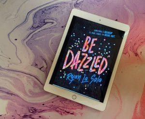 the cover of Be Dazzled by Ryan La Sala is displayed on a white iPad sitting on top of a purple, white and pink marbled counter.