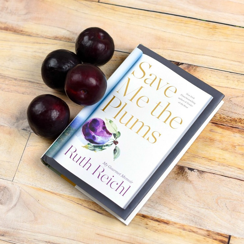 A copy of Save Me the Plums by Ruth Reichl sits next to plums