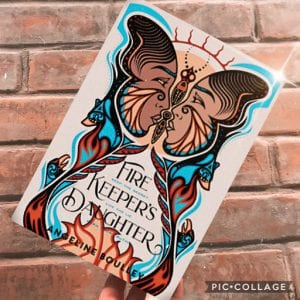 : Cover of the book Fire Keeper's Daughter by Angeline Boulley is held against a brick wall