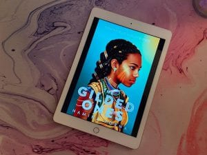the cover of The Gilded Ones by Namina Forna is displayed on a white iPad sitting on top of a