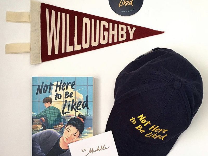 A copy of Not Here to Be Liked with a signed book plate, a black hat embroidered with Not Here to Be Liked, a Willoughby High School pennant, and a round black sticker that says Not Here to be Liked.