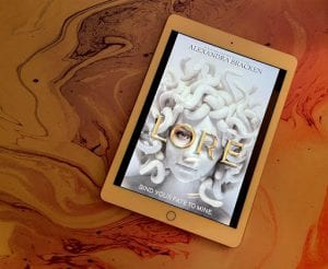 = the cover of Lore by Alexandra Bracken is displayed on a white iPad sitting on top of a purple, white and pink marbled counter.