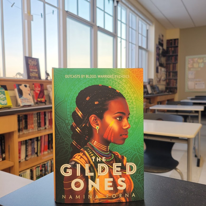 A copy of The Gilded Ones in a classroom