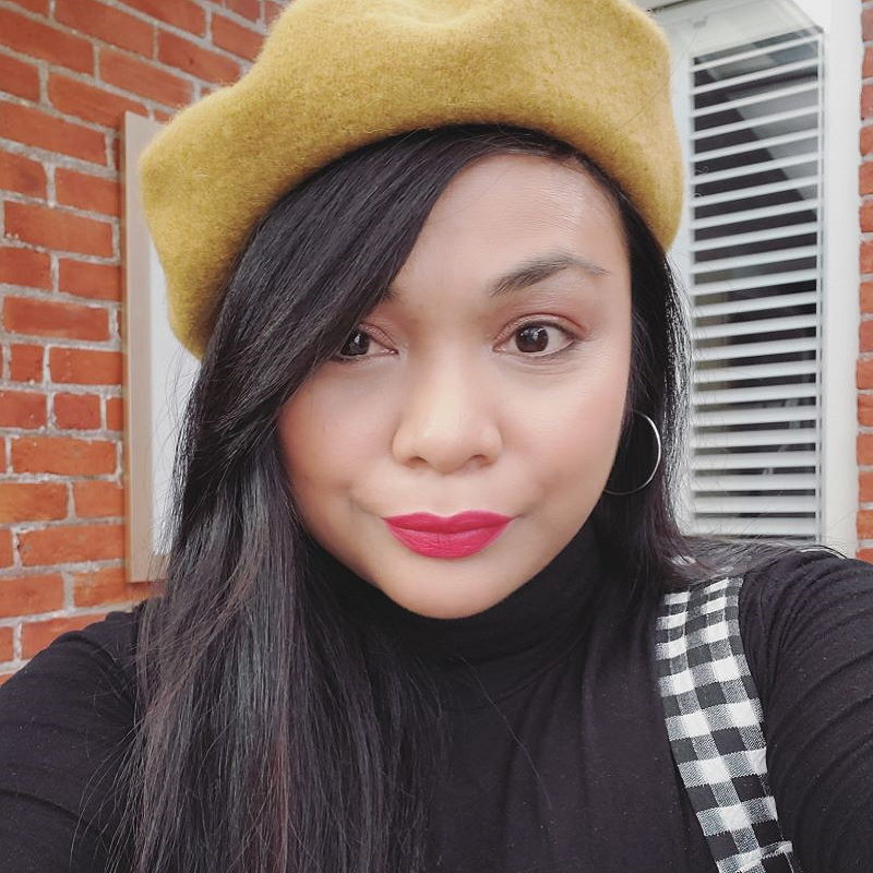 Vanessa is wearing a black, long-sleeve turtleneck under a black and white checkered tank top. She has a silver hoop earring visible in her left ear. Her long brown hair is over her right shoulder. She has a yellow beret on her head and is wearing red lipstick. Vanessa is standing in front of a red brick building, with a white windowpane visible.