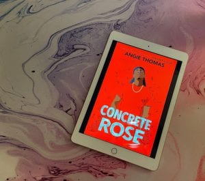 the cover of Concrete Rose by Angie Thomas is displayed on a white iPad sitting on top of a purple, white and pink marbled counter.