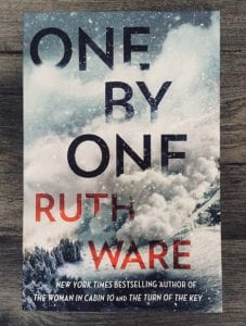 On a wooden surface, the book One by One by Ruth Ware lies flat in the centre.