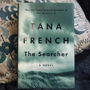 The book, The Searcher by Tana French, sits on a chair against a white pillow detailed with turquoise embroidery starting in the top left, covering three-quarters of the frame. In the bottom right-hand corner, a blue blanket is visibl