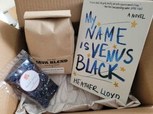 an open box with a book, chocolate wrapped in cellophane and a bag of coffee. Loose packing material lines the bottom of the box.