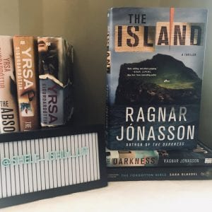 Cover of the book The Island by Ragnar Jonasson standing on two books, with a sign that says @shelf_ishly_lit in front of three books;