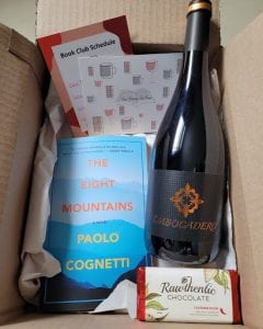 an open box that includes a book, bottle of wine, chocolate in package and info card;