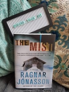 : Cover of the book The Mist by Ragnar Jonasson leaning against pillows and blanket with a sign that says @shelf_ishly_lit;