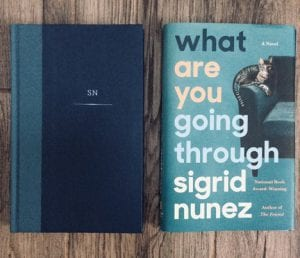 On a wooden surface, two items are laying flat. On the left, a hardcover copy of the book What Are You Going Through by Sigrid Nunez sits without its book jacket cover. On the right is the book jacket cover.