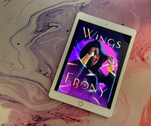 the cover of Ebony by J. Elle is displayed on a white iPad sitting on top of a purple, white and pink marbled counter.